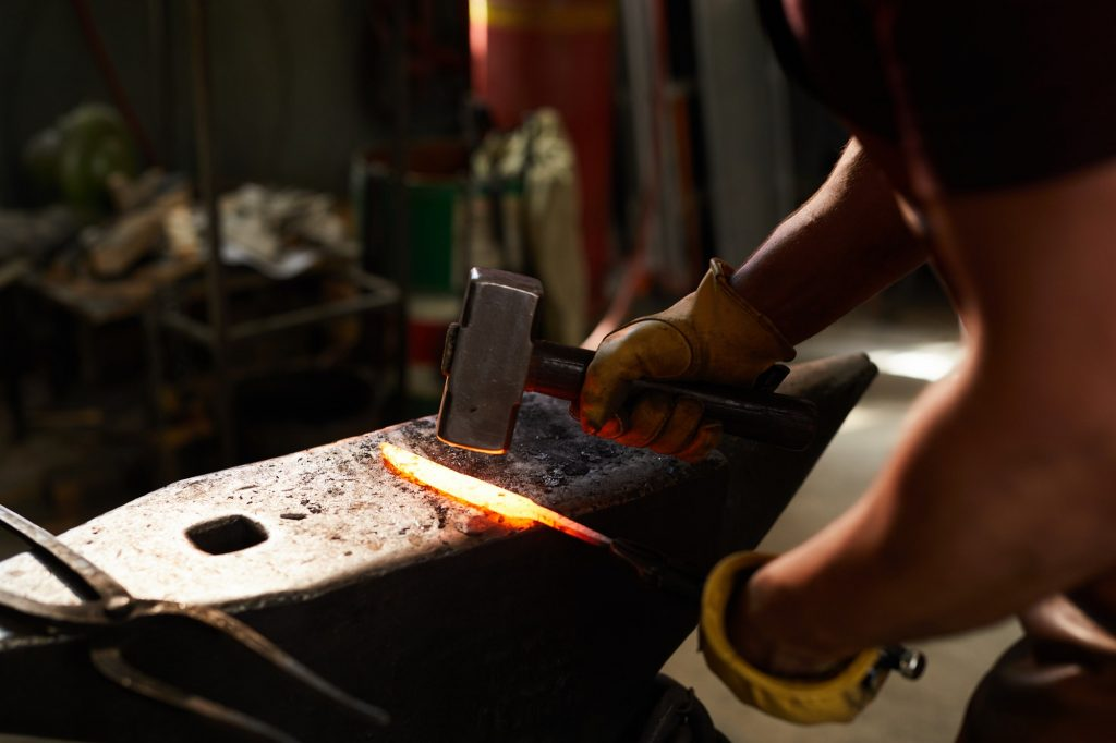 Blacksmith shaping heated metal bar