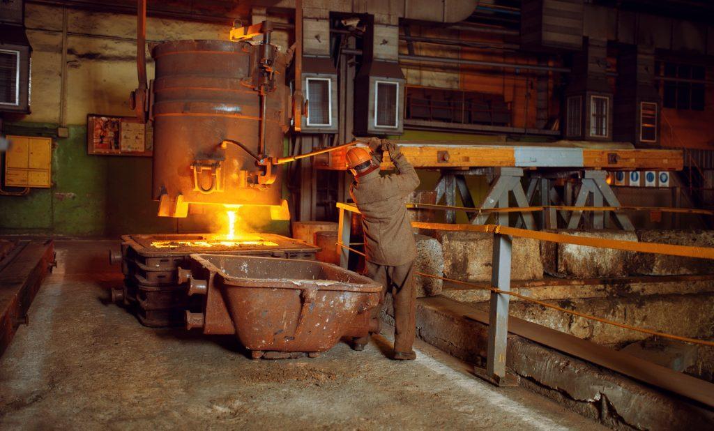 Steelmaker pours liquid metal from basket, factory